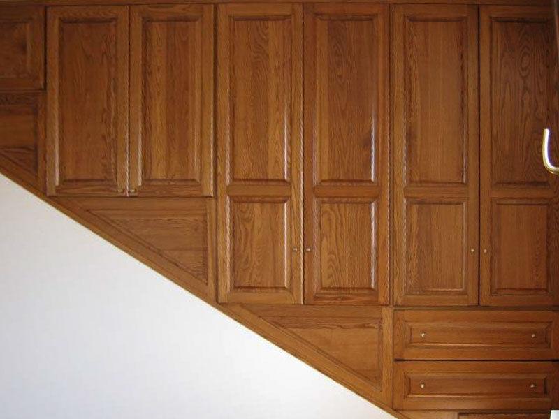 Armadio a parete su misura in castgno massello realizzato in un vano scale con otto ante apribili e 3 cassetti. Sportelli in massello bugnati, tinta noce medio. Cernire e pomoli in ottone dorato