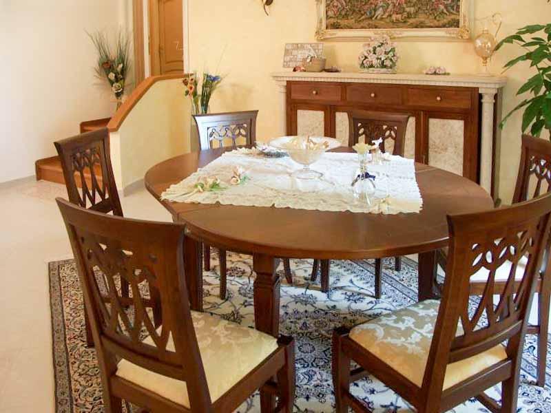 Tavolo ovale in noce con piano intarziato allungabile misure chiuso: 140x100 aperto:180x100, sedie modello goccia sempre in noce con seduta rivestita in stoffa
