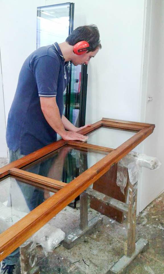 Sostituzione dei vetri in un infisso durante il restauro